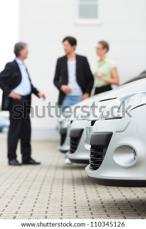 Two men man and one woman stand behind a row of silver-metallic cars on a parking place on yard of dealer - stock photo