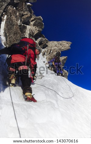 Two men mountain climbing snow and rock on Arete du Cosmique in Chamonix France
