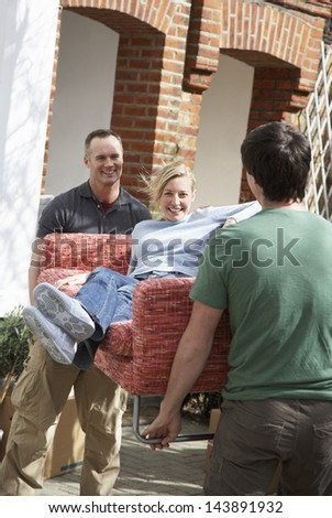 Two men outside house carrying woman on sofa - stock photo