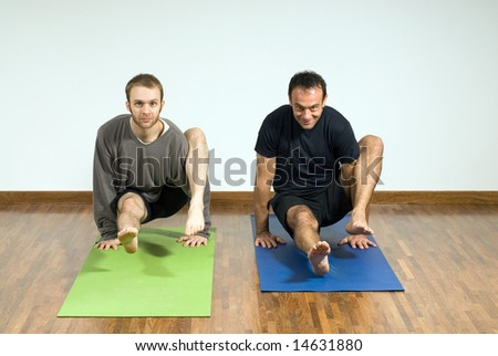 Two men performing yoga together. Hovering position supported by arms. Horizontally framed shot. - stock photo