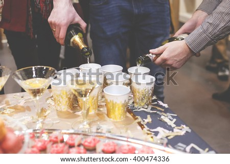 Two men pouring champagne in brilliant glasses at the celebration. Job waiter-bartender. Table with sweet and glasses of champagne. - stock photo