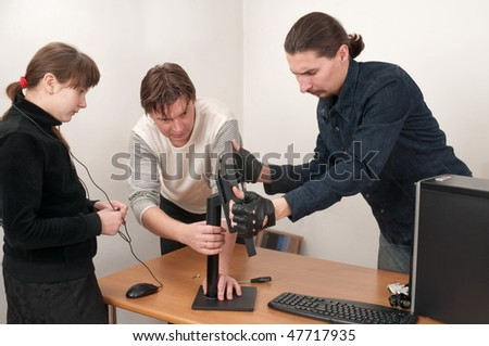 Two men prepare the computer for connection, and the girl observes. A family. - stock photo