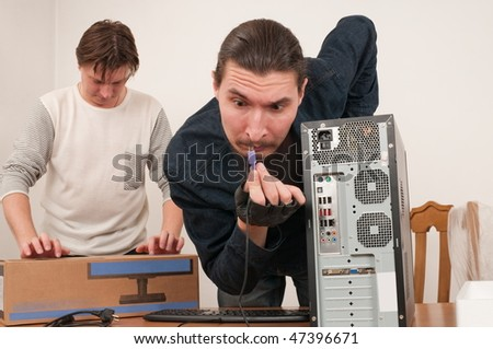 Two men prepare the new computer for connection. - stock photo