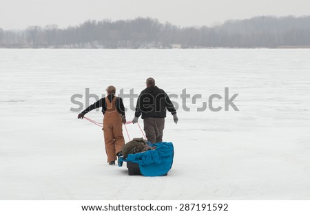 Two men pull sled filled with ice fishing equipment across frozen lake - stock photo