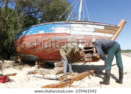 Two men repair a hole in the hull of a damaged wooden fishing boat in rural Africa. - stock photo