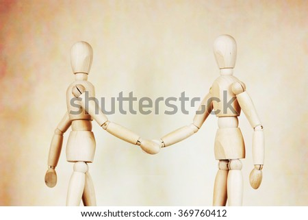 Two men shake hands to each other. Abstract image with wooden puppets - stock photo