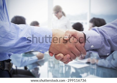 Two men shaking hands against business people in board room meeting - stock photo
