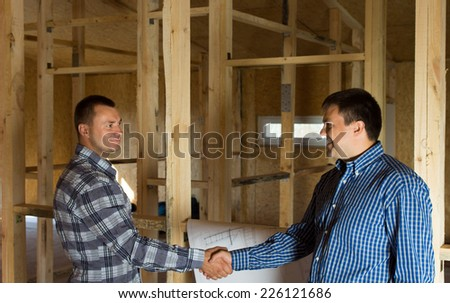 Two men shaking hands in a half constructed timber frame house with a building blueprint alongside them as they signal their satisfaction with the progress - stock photo