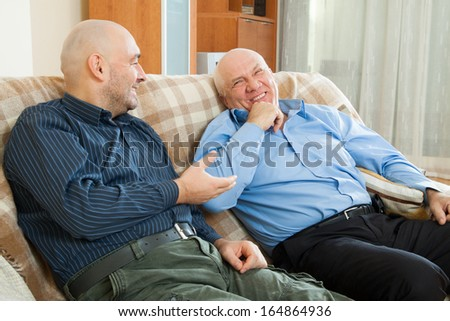 Two men siting on  couch at home - stock photo