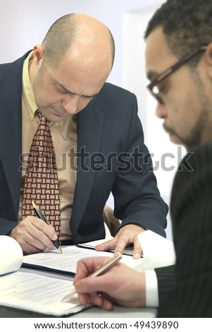 Two men sitting at a table at each other, sign the contract