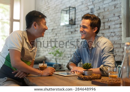 Two Men Sitting at Cafe, Asian Mix Race Friends Guys Happy Smile Natural Light - stock photo