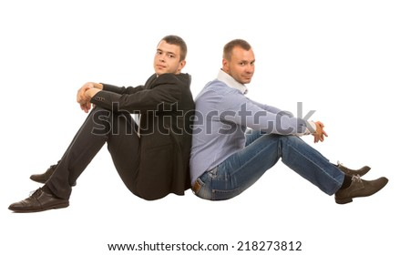 Two Men Sitting Back to Back Looking at Camera in Studio with White Background - stock photo