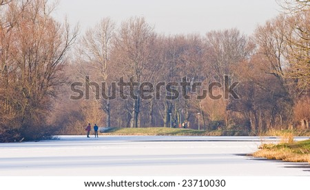 Two men skating on the ice in the sunshine