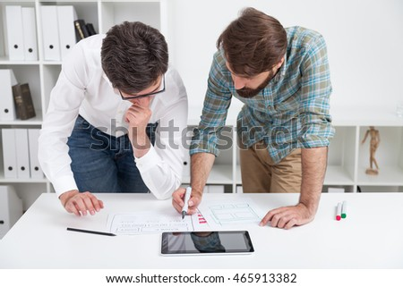 Two men standing near table and discussing current task. Concept of working together.