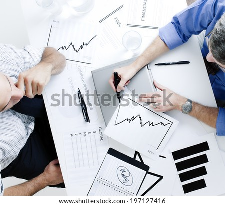 Two men studying charts over a table with laptop and open agenda.