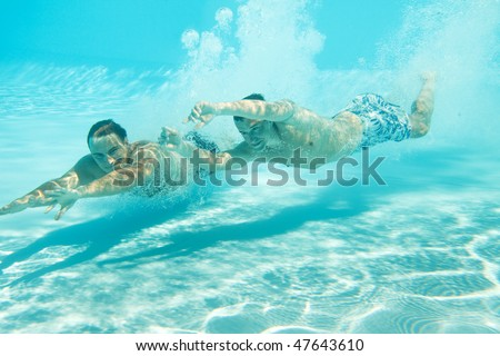 Two men swimming with open eyes underwater in pool - stock photo