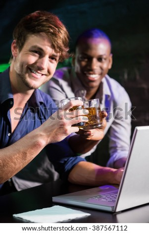 Two men toasting their whiskey glasses at bar counter while using laptop - stock photo