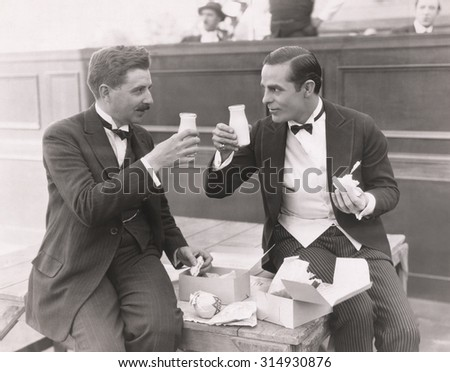 Two men toasting with milk bottles - stock photo