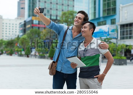 Two men tourists taking selfie photo smile, asian mix race friends guys outdoor city street - stock photo