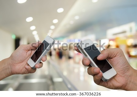 Two men using mobile smart phone with blurred background of department store, communication concept, transaction concept. - stock photo