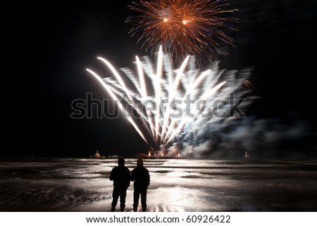Two men watching watching fireworks at the sea (taken at the International fireworks festival of the Hague 2010) - stock photo