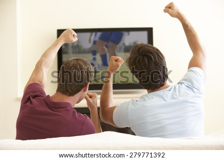 Two Men Watching Widescreen TV At Home - stock photo