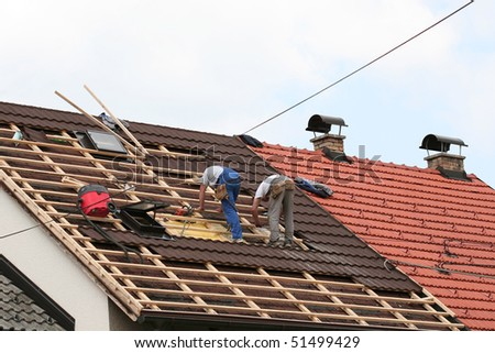 Two men working on the roof - stock photo