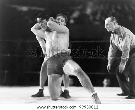 Two men wrestling with referee making a call in the background - stock photo