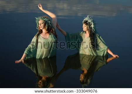 Two mermaids on the forest lake - stock photo