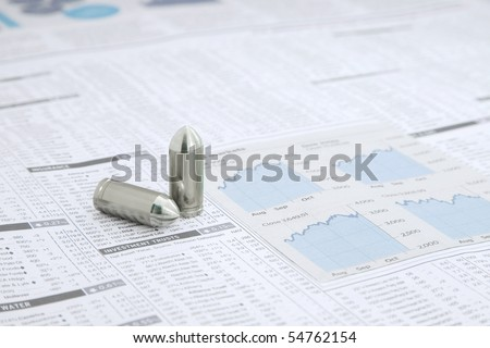 Two metal Bullets on a News paper Stock market financial page showing stocks and shares - stock photo