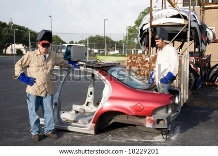 Two metal factory workers taking a smoke break in the scrap yard. - stock photo