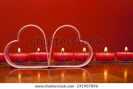 Two metal hearts on the background of  burning candles  - stock photo