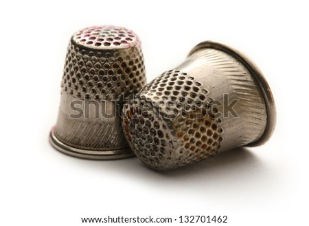 Two metal sewing thimbles on white - stock photo