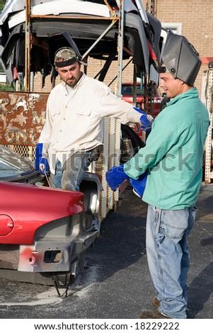 Two metal workers in the scrap metal yard. - stock photo