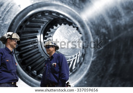 two metal workers, mechanics in front of large cogwheels axle, symbolic with steel industry - stock photo