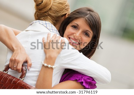 two mid adult colleagues hugging outdoors and looking at camera
