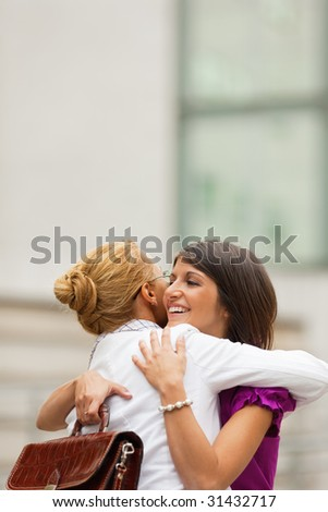 two mid adult colleagues hugging outdoors. Copy space - stock photo