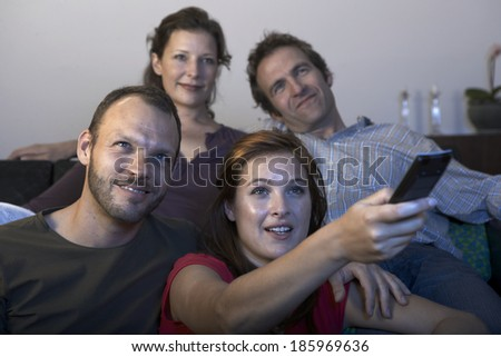 Two mid adult couples watching TV - stock photo