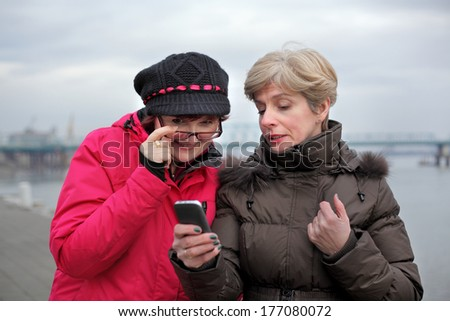 Two mid adult woman friends  looking to mobile phone - stock photo