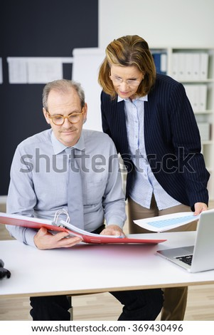 Two middle-aged business colleagues, a man and woman, working together reading a set of documents in a file or binder with serious expressions