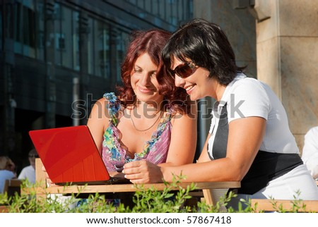 Two middle-aged women sitting in a cafe in downtown,and watching something in laptop