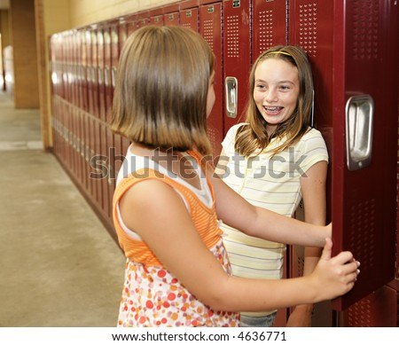 Two middle school students chatting at their lockers. - stock photo