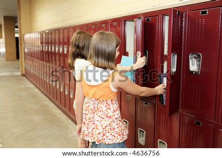 Two middle school students visiting their lockers between classes. - stock photo