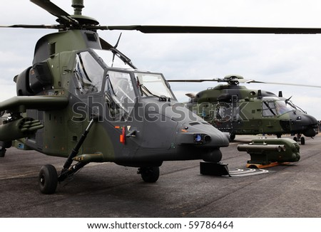 Two military aircrafts with missiles (a Tiger scout and a transportation helicopter). - stock photo