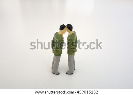 Two miniature figures, a couple of men, meaning homosexuality or sharing a secret - stock photo