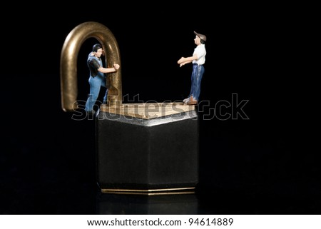 Two miniature figurines of workmen stand on the top of a padlock with the shackle open testing the strength in a safety and security concept. - stock photo