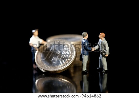 Two miniature toy model businessmen shake hands standing in front of a pile of Euro coins and workman, symbolic of new economic strategy - stock photo