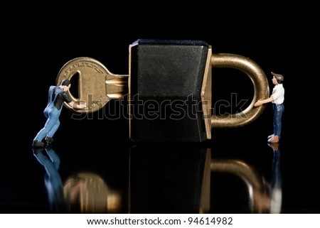 Two miniature workmen checking a key and padlock on black background with reflection, conceptual of a safety and security check - stock photo