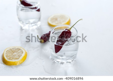 two misted glasses with cold vodka whis lemon and chilyr on an white wooden table