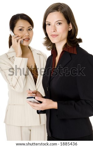 Two modern businesswomen using mobile phones and PDA